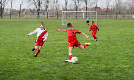boys  kicking football on the sports field Stock Photo