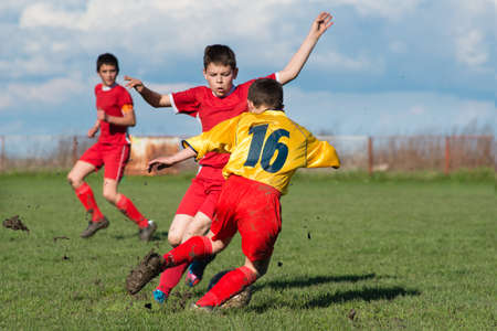 boys  kicking football on the sports field Stock Photo