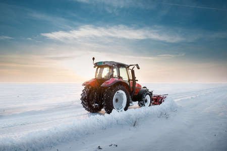 Tractor cleaning snow in sunset photo