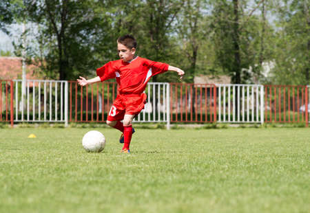 boys only: Little Boy playing soccer on the sports field Stock Photo