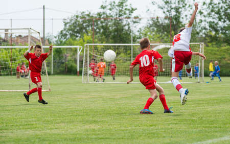 chicos pateando el f?l en el campo de deportes Foto de archivo