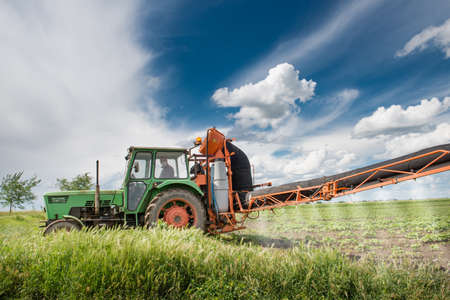 tractor spraying pesticides on soy bean photo