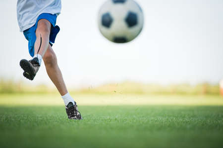 soccer ball on grass: Little Boy Shooting at Goal Stock Photo