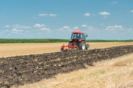 furrows: Tractor plowing the stubble field