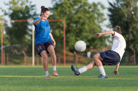 young womens: two female soccer players on the field