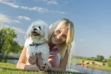 girl and dog lying on the grass photo