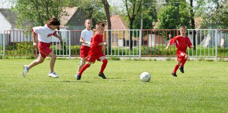 10 to 12 years: boys  kicking football on the sports field Stock Photo