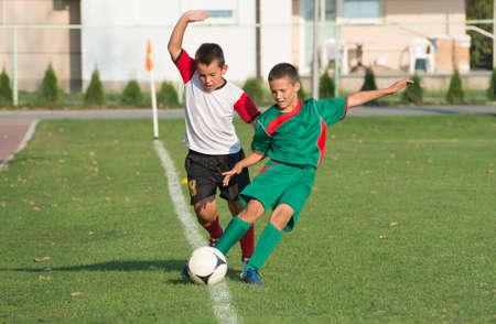 arbiter:  little boy play defense on football match