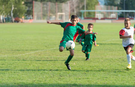 little boy kicking the ball on football match photo