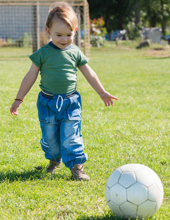 babyhood: little child playing with ball on football field Stock Photo