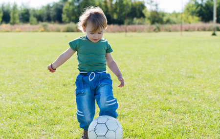 little child playing with ball on football field photo