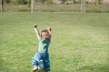 very happy little boy playing with ball on football field photo