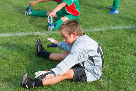 spread legs: goalkeeper do stretching before football match Stock Photo
