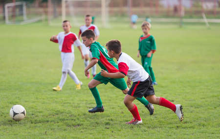 soccer ball on grass: kids running with ball on football match