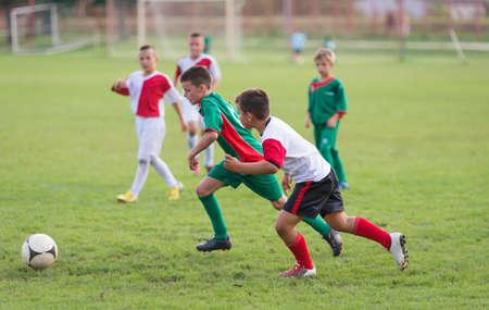 Niños corriendo con balón en partido de fútbol