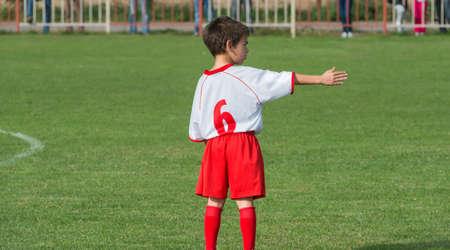 little boy organize defense on football match photo