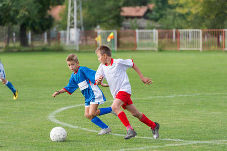 jugando futbol: niños pequeños jugando ofensiva en partido de fútbol