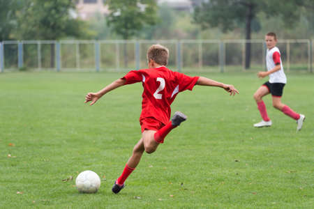 little boy kicking the ball in the game photo