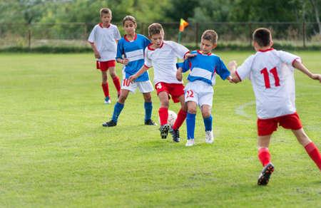 kleine kinderen spelen verdediging in voetbalwedstrijd