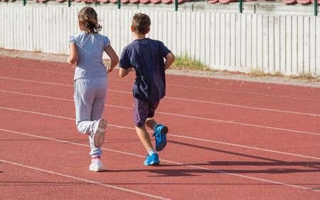 girl and boy jogging on tartan track