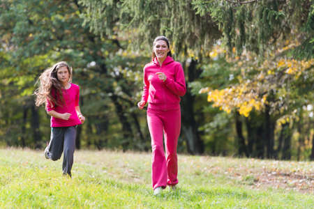 Two girls running on a meadow photo