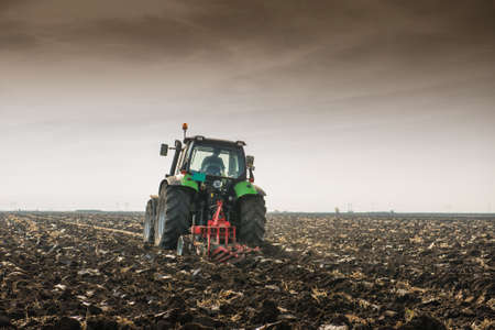 wheel tractor: Tractor plowing field in autumn Stock Photo