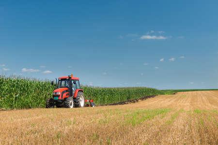 Tractor ploegen het stoppelveld