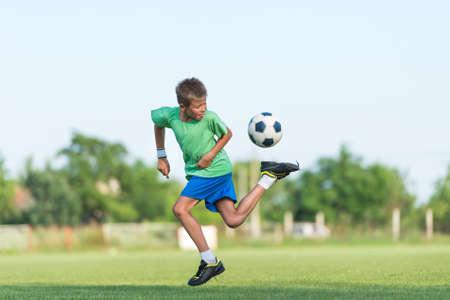 jugando futbol: niño corriendo goteo en el campo deportivo