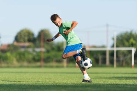 dribbling: little boy running dribbling on the sports field Stock Photo