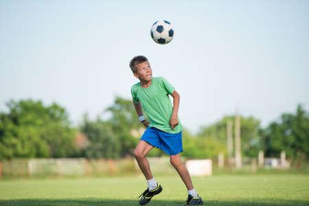 boy ball: little boy running dribbling on the sports field Stock Photo