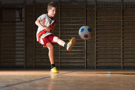 boy ball: Little Boy Shooting at Goal Stock Photo