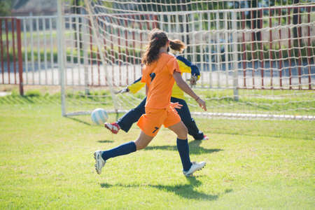 women playing soccer: Female soccer player kicking at goal Stock Photo