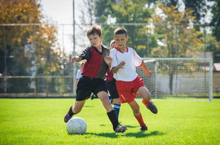 kicking ball: boys  kicking football on the sports field Stock Photo