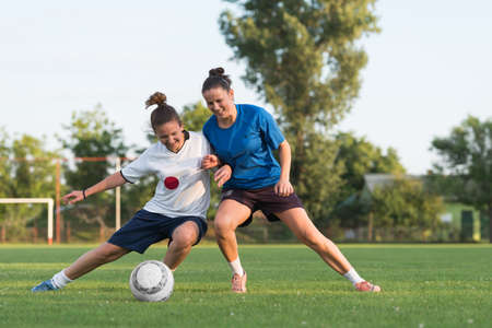 football kick: two female soccer players on the field