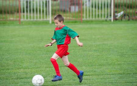 football socks: boy kicking football on the sports field Stock Photo
