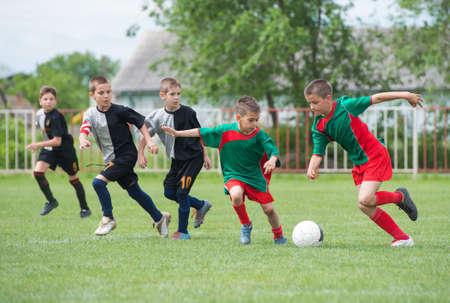 jongens schoppen voetbal op het sportveld