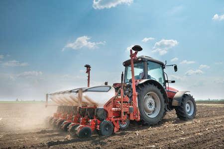 トラクターとフィールドで作物を植える種をまく人