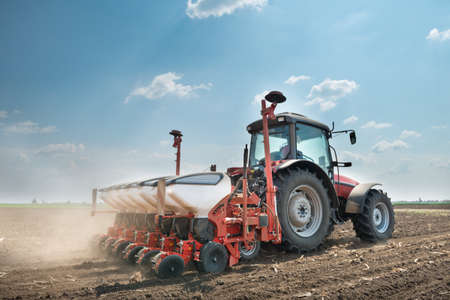 agricultural equipment: tractor and seeder planting crops on a field Stock Photo