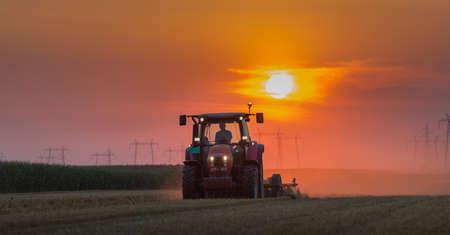 arando: tractor arando campo al atardecer