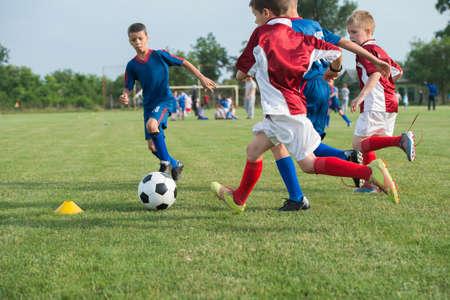 kinderen: jongens schoppen voetbal op het sportveld