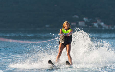 water sport: young woman water skiing on a sea Stock Photo
