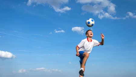 gelukkige jongen spelen voetbal op hemelachtergrond