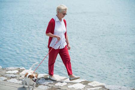 Senior woman walking her dog photo
