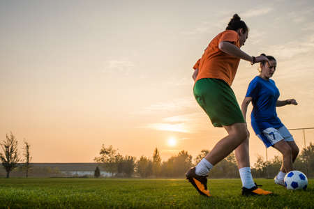 two woman: two female soccer players on the field