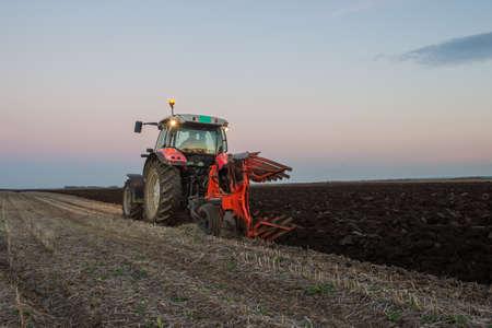 arando: Tractor arando al atardecer