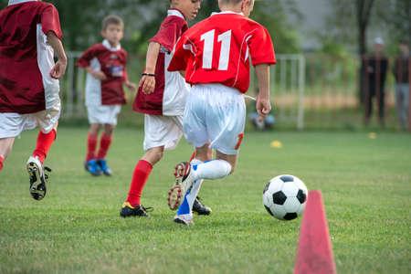 Jongens schoppen voetbal op het sportveld Stockfoto