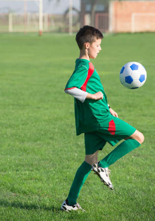 soccer boots: Child playing football on a soccer field