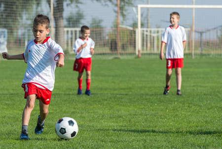 rivals rival rivalry season: Boys kicking football on the sports field Stock Photo