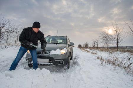 stuck up: man digging up stuck in snow car Stock Photo