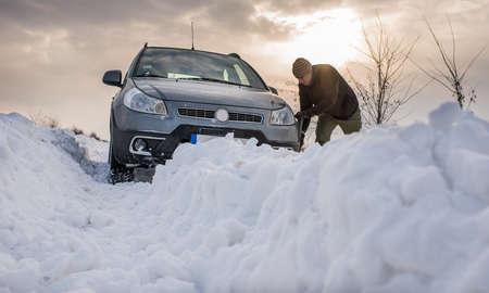 man digging up stuck in snow car Stock Photo